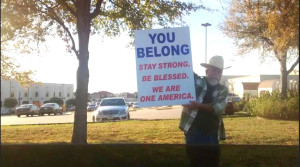 Man holding 'You belong' sign outside North Texas Islamic Center